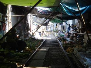 The train arrives in the middle of this market in Ratchaburri, Thailand