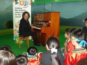 "Snuggled together by the piano, Julie Gold sang her grammy-award winning song ""From A Distance."""